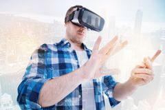 Young man zooming in content on transparent tablet. Augmented reality. Stocky middle-aged man using VR headset and working on a transparent tablet zooming in a Royalty Free Stock Photos