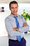 Young manager in formals standing with arms crossed Stock Image