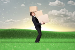 Young manager holding pile of pasteboard boxes. Nature background Stock Photos