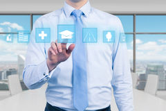A young manager in modern panoramic office is pushing the educational icon. A concept of business education. Stock Photo