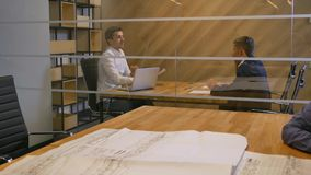 Young manager offering new mortgage contract to married couple. Young manager offering new mortgage contract to married couple inside of modern office glass stock footage