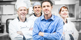 Young manager posing with some chefs Stock Photo
