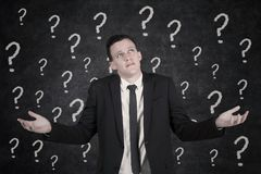 Young manager with question marks stock photography