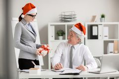 Surprise for boss. Young manager in Santa cap making xmas surprise to her boss at work Royalty Free Stock Images