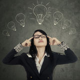 Young manager seek inspiration. Portrait of female manager seeking inspiration or idea under lightbulbs Royalty Free Stock Photo
