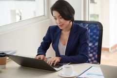Businesswoman working on laptop at office. Young manager sitting at the table and typing on laptop computer during her work day at office stock images