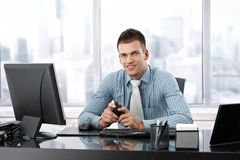 Young manager smiling at desk Stock Photo