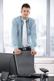 Young manager standing in office smiling Royalty Free Stock Image