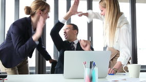 Young manager and two businesswoman with laptop, high-fiving and cheering stock footage