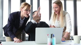 Young manager and two businesswoman with laptop, high-fiving and cheering. Close up of handsome young manager and two attractive businesswoman with laptop in stock footage