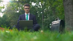 Young manager working on laptop in forest, enjoying nature, escape from office. Stock footage stock video