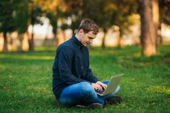 The young manager working on a laptop in the park. Lunch Break. Stock Image