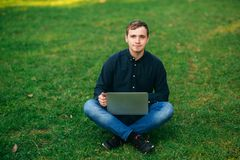 The young manager working on a laptop in the park. Lunch Break. Royalty Free Stock Photography