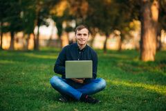 The young manager working on a laptop in the park. Lunch Break. Stock Photo