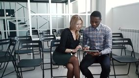 Young managers communicate, using tablet in large company. African man and woman are sitting and looking at screen of multimedia device attentively, touching stock video footage