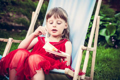 Young mannered girl in red dress relaxing in chaise lounge eat cake during outdoor party in the garden. Young mannered fashion model girl in red dress relaxing Royalty Free Stock Images