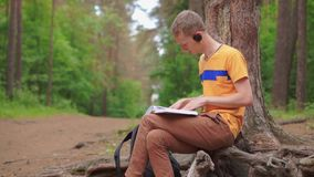 A young manputs on his headphones and reads a book while listening to music. A young man in the forest puts on his headphones and reads a book while listening stock video