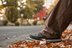 Young Mans Feet In Autumn Leaves on Ground By Curb In City Street. Selective Focus Bokeh Background With Copy Space Stock Image