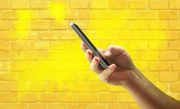 Young mans hand holding mobile phone against yellow brick wall stock photo