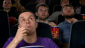 Young mans watching movie at cinema: thriller. Company young mans watching movie at cinema: thriller, all worry, eating popcorn stock video