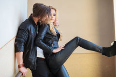Young mant is whispering something to his lover. Young men in leather jacket is whispering something to his lover while embracing her Royalty Free Stock Images