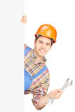 Young manual worker with helmet holding a wrench Royalty Free Stock Image