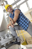 Young manual worker holding wrench in industry Stock Photo