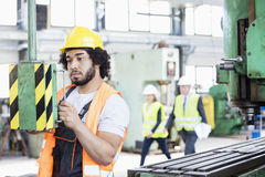 Young manual worker operating machinery in metal industry royalty free stock photos