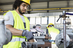 Young manual worker operating machinery in metal industry stock photography