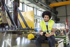 Young manual worker using mobile phone in metal industry royalty free stock photo