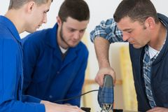 Young manual workers in protective workwear cutting metal in industry royalty free stock photography