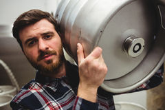 Young manufacturer carrying keg in brewery Royalty Free Stock Images