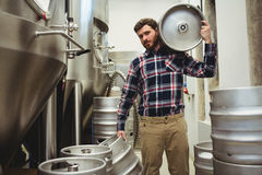 Young manufacturer carrying kegs in brewery Stock Photo