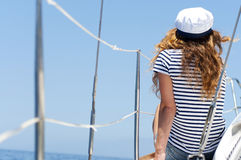Young marine style woman is sitting on the boat and looking forward Royalty Free Stock Image