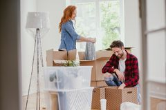 Young marriage packing stuff into boxes during relocation to new home. Concept stock photos
