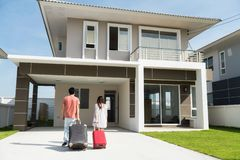 Asian couple move to new house. Young married Asian couple moving in a new buying modern house. Happy husband and wife pull luggage and walk to home entrance royalty free stock photo