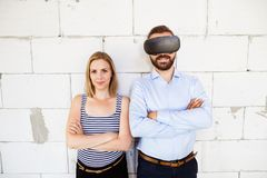 Young married couple at the construction site. Young married couple or architects at the construction site. Man wearing virtual reality goggles Royalty Free Stock Photo
