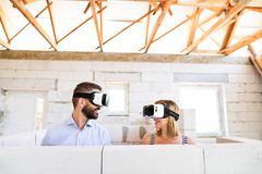 Young married couple at the construction site. Young married couple or architects with virtual reality goggles at the construction site Stock Images