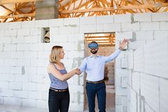 Young married couple at the construction site. Young married couple or architects with virtual reality goggles at the construction site Stock Photo