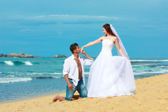 Young married couple  on a beach in a tropical destination. Young pretty bride wearing a wedding dress and groom in a white shirt on the beach of a tropical Stock Images