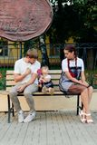 Young married couple on bench in park, mother with daughter with lollipop in hands in one-year dresses Stock Image