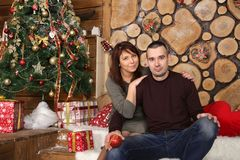 Family couple at christmas tree with gifts. Young married couple at christmas tree with gifts, portrait in a beautiful festive interior Royalty Free Stock Photos