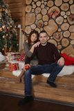 Family couple at christmas tree with gifts. Young married couple at christmas tree with gifts, portrait in a beautiful festive interior Royalty Free Stock Images