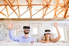 Young married couple at the construction site. Young married couple or architects with virtual reality goggles at the construction site Stock Photography