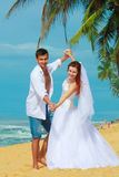 Young married couple dancing on a beach in a tropical destination Stock Photography