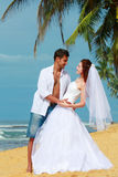 Young married couple dancing on a beach in a tropical destination. Young pretty bride wearing a wedding dress and groom in a white shirt on the beach of a Royalty Free Stock Photography