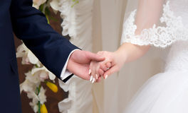 Young married couple holding hands. Ceremony wedding day royalty free stock image