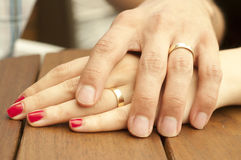 Young Married Couple Holding Hands Closeup. A closeup of a young married couple holding hands on a wooden table Royalty Free Stock Photography