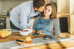 Young married couple in kitchen.Pregnant woman is sitting at table, man is holding her pregnant belly and kisses stock images
