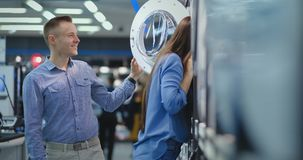 Young married couple man and woman in appliances store choose to buy a washing machine for the house. Open the door. Looking into the drum, compare the design stock footage